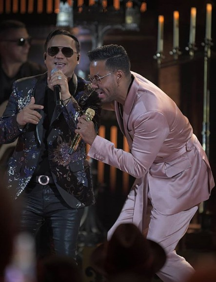 Romeo Santos signing song with his male co-singer