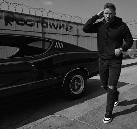 Julian Edelman posing with a car