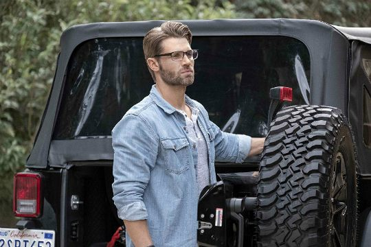 Courtney Vogel's husband, Mike Vogel posing with his jeep