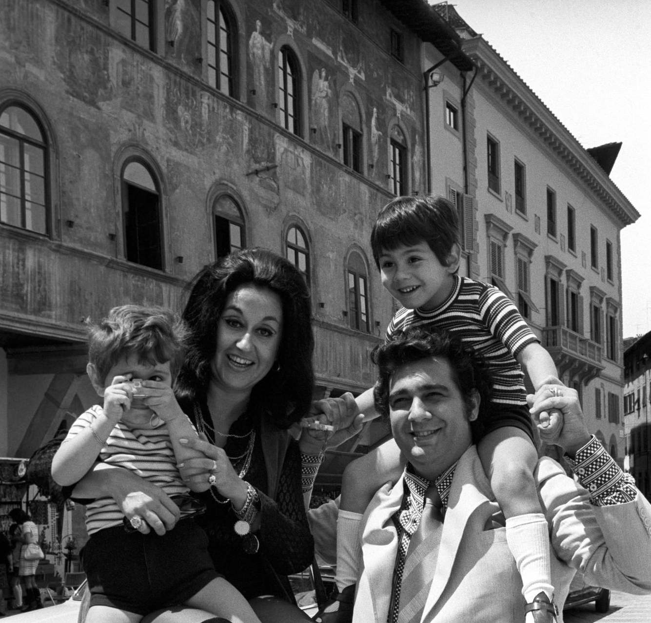 Mexican soprano Marta Ornelas holding her son Alvaro Domingo with a toy camera in the hands in front of Palazzo dell'Antella on piazza Santa Croce. Beside her, her Spanish husband and tenor Placido Domingo smiling while carrying piggyback their son and Mexican singer Placido Domingo Jr. Florence, 1970s