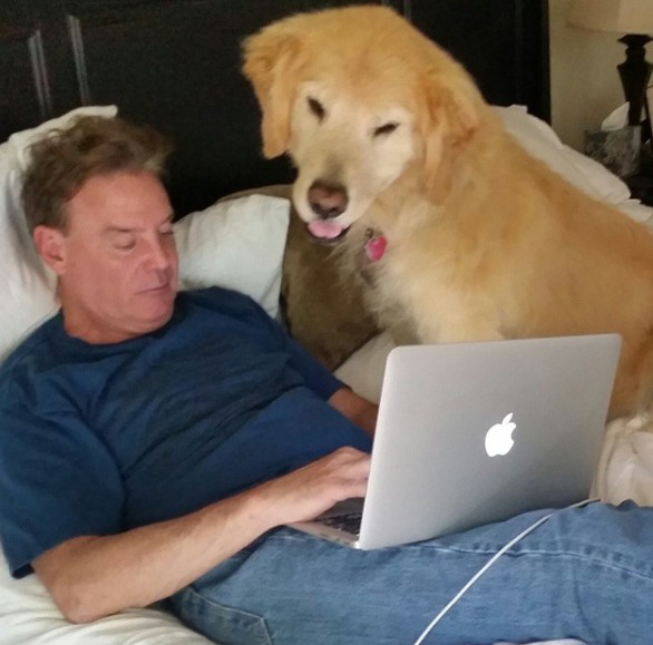 Mark Kriski working in home with his laptop along side his dog