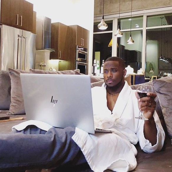 Derrick Jaxn posing for a photo sitting inside his home with laptop