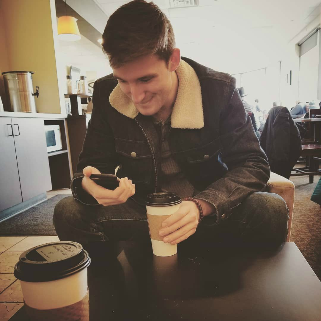 Michael Boxleitner using his phone with coffee in hand