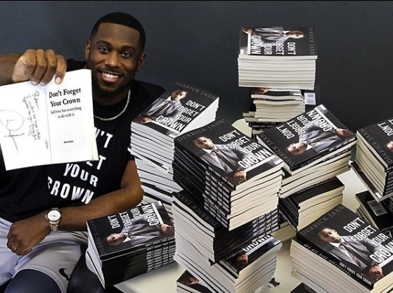 Derrick Jaxn posing for a photo with his book