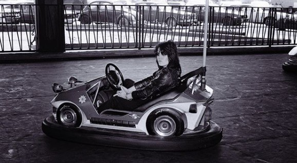 Joan Jett driving playing car in the fun park