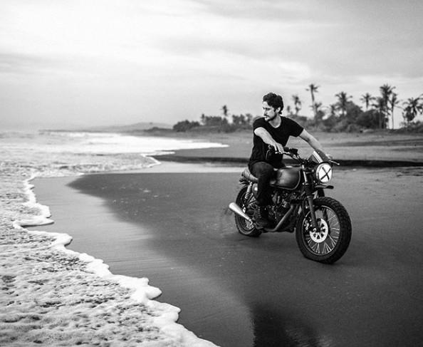 Peter Gadiot riding his bike on beach