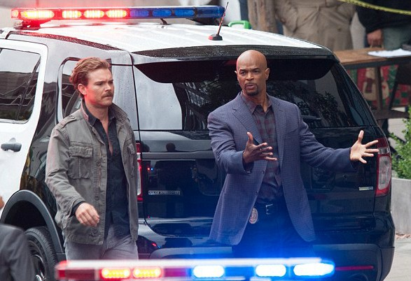 Kyla Wayans' father Damon acting with his co-actor with police car in the background