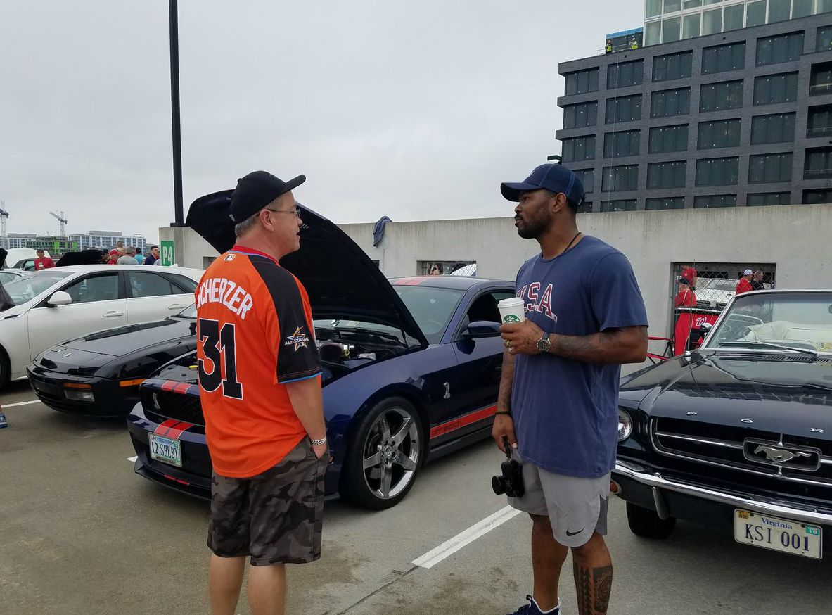 Howie Kendrick talking to his friend while cars in the backgrounds