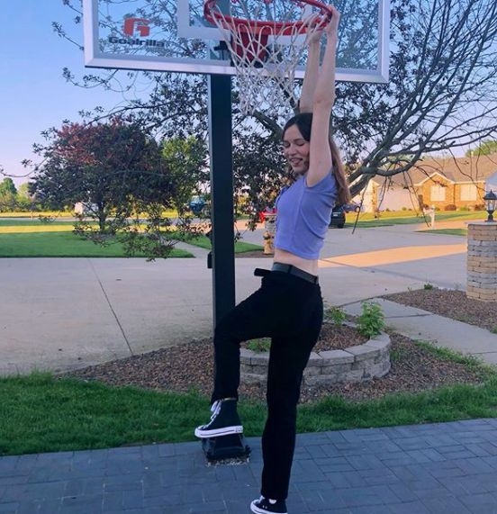 Claire Drake hanging in the basketball pole