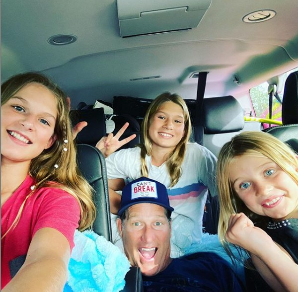 Danny Kanell clicking selfie sitting inside his car with his daughters