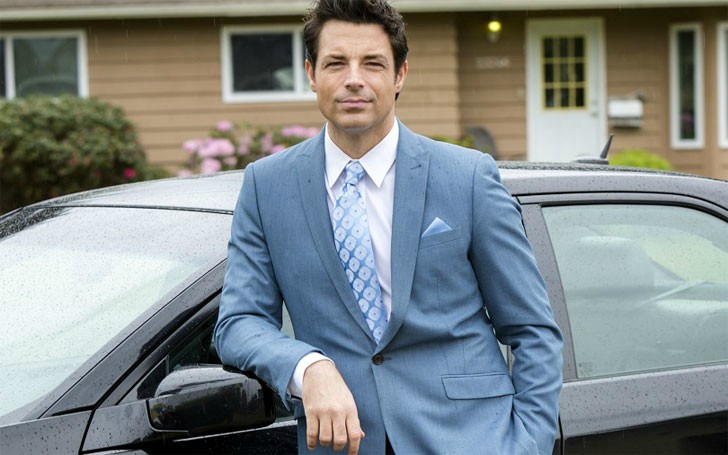 Brennan Elliott posing for a picture with car in the background