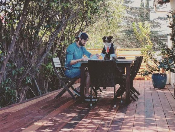 James Lafferty sitting in a table with his dog