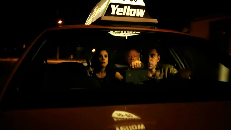Carly Pope sitting inside taxi with gun in hand with her co-actors