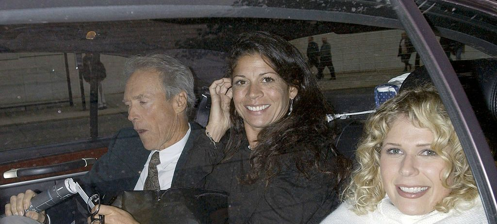 """Clint Eastwood his ex-wife, Dina Ruiz, and a friend sit in the back of a car after a news conference at Walter Reade Theater to promote the film """"Mystic River"""" at Lincoln Center October 1, 2003 in New York City."""