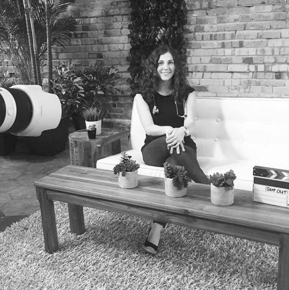 Dr. Lauren Thielen sitting on sofa and posing for a picture