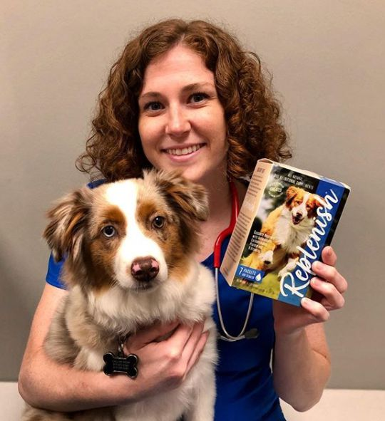 Dr. Lauren Thielen posing for picture with dog and their products