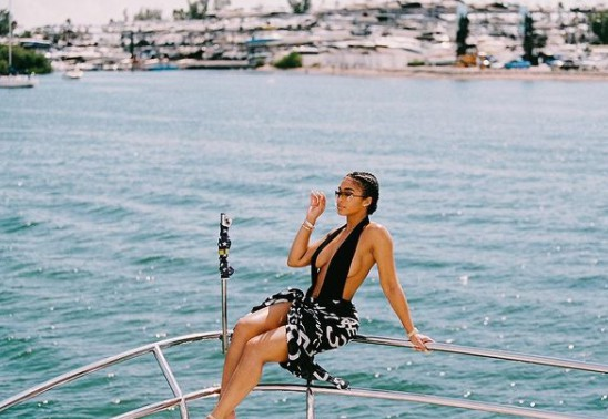 Lori Harvey sitting on a boat and posing for photo