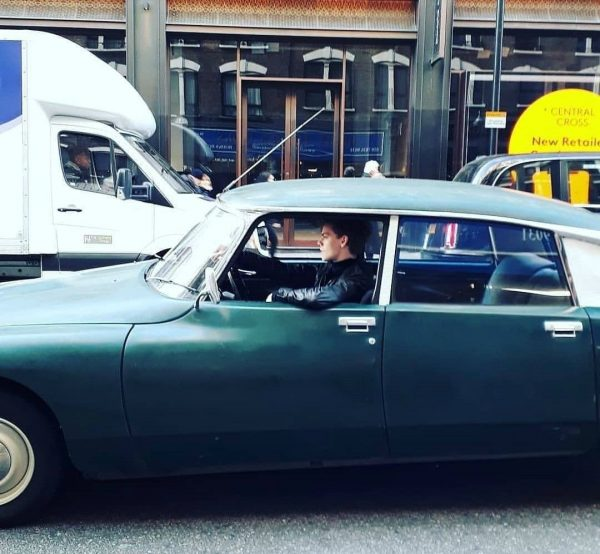 Thomas Brodie-Sangster sitting inside the car