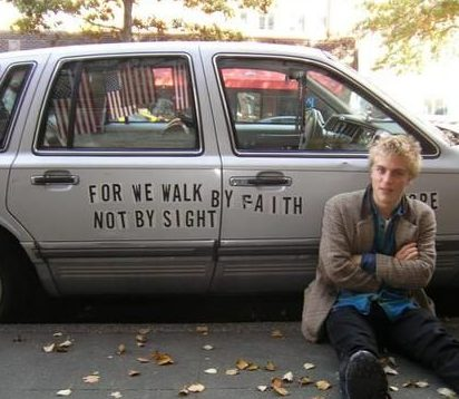Johnny Flynn posing for a photo with his car