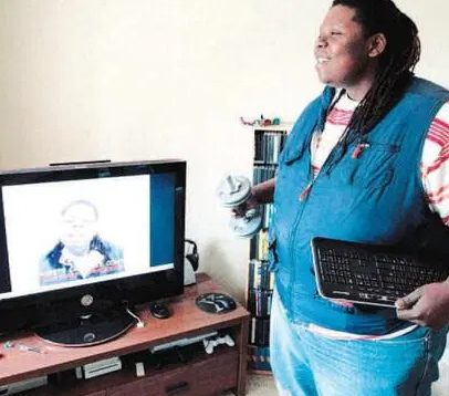 Jumoke Hill posing for a photo with his Laptop