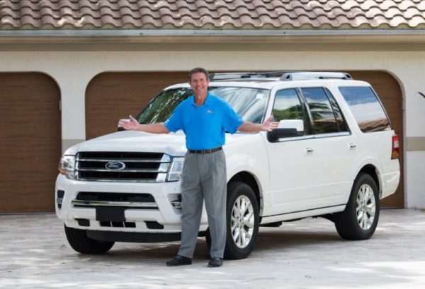 Dan Marino posing for a photo with his car